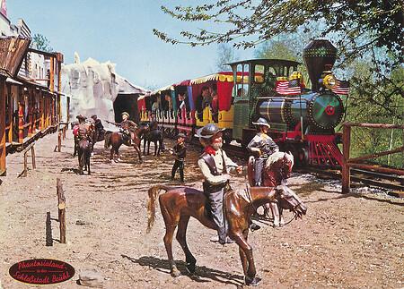 Pacific-Western-Express der an Cowboys auf Pferden vorbei fährt.